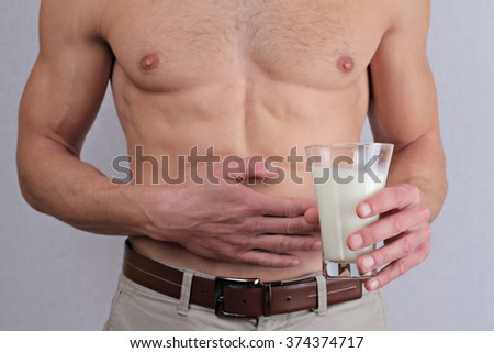 Man with stomach pain holding a glass of milk. Dairy Intolerant person. Lactose intolerance, health care concept.