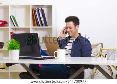 man with the mobile phone and the folder on the desktop in the home or office