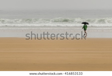 Man with umbrella walking along the beach