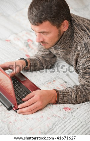 Man working on his laptop computer at home