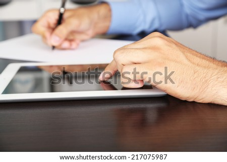 Man working on tablet on wooden background closeup