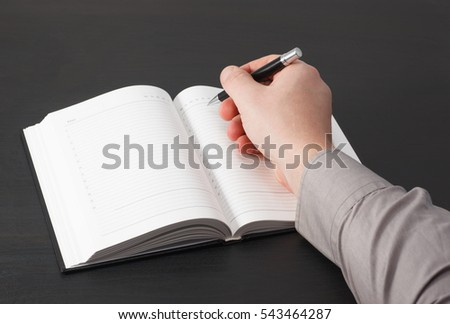 Man Writings Note on his Notebook. Black background.