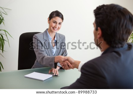Manager shaking the hand of a customer in her office