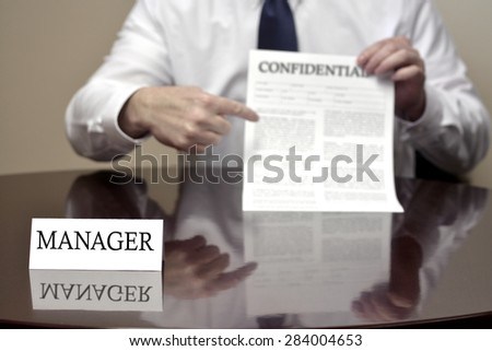 Manager sitting at desk holding Confidential document for deal