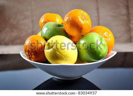Mandarins, oranges, apples and lemons in a ceramic bowl, on a home background