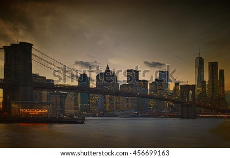 Manhattan skyline with Brooklyn Bridge at twilight.