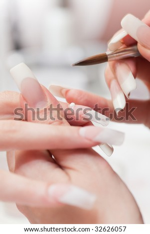 Manicurist treating client at beauty salon. Manicure, painting on nail