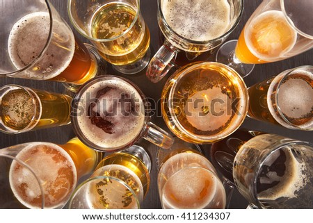 Many different beer glasses with beer from all over the world