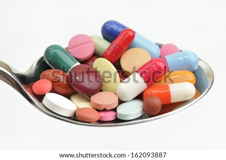 Many different colored tablets and pills on a spoon isolated in white background. Abuse or addiction of drugs.