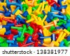 Many different toy puzzle mosaic pieces laying in a pile - stock photo