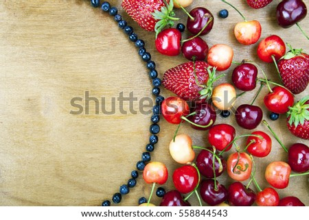Many fresh fruit lying around the semi-circle of blueberries on a wooden boards background