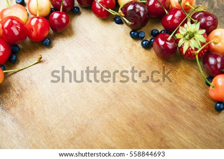 Many fresh fruits lie on a wooden boards background