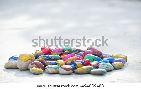 Many small pebbles covered with multicolored paint lie on the surface close-up