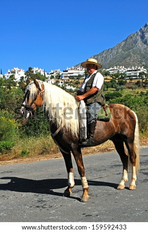 MARBELLA, SPAIN - JUNE 8, 2008 - Man riding a horse during the Romeria San Bernabe Religious Festival, Marbella, June 8, 2008.