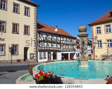 market place wit fountain and  half timbered houses in fairy tale town of Steinau