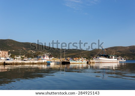 Marmari port with anchored fish boats and white houses against a blue sky and blue waters in Evia, Greece