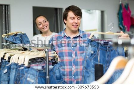 Married couple choosing blue jeans in a clothing department of a mall