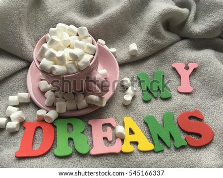 Marshmellows and wooden word my dreams. Dreams wooden letters on grey blanket.