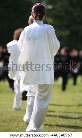 martial arts Tai Chi with shiny white silk dress during the concentration exercises and relaxation in the large public park
