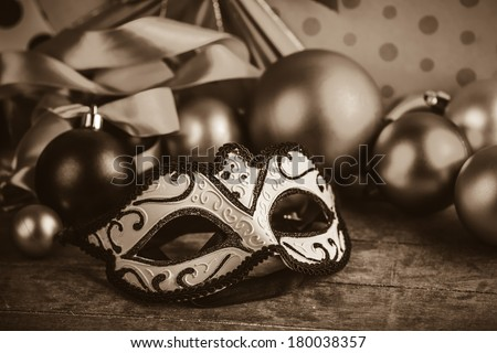 Mask for carnival near gifts. Photo in old color image style