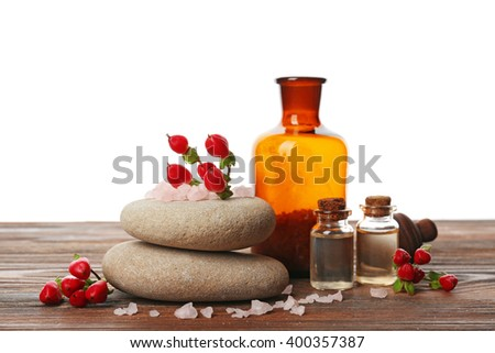 Massage oil and pebbles on wooden table against white background
