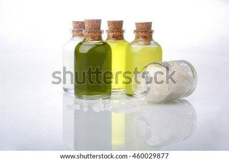 Massage oil bottles and sea salt with reflection