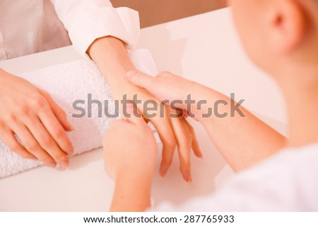 Masseuse massaging hand