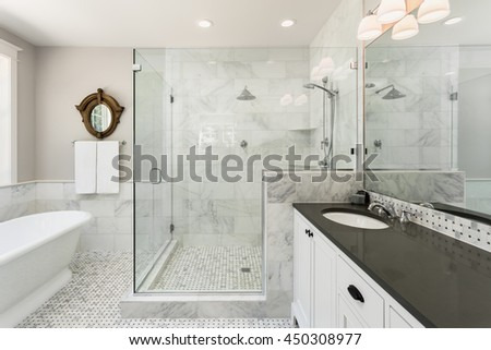 Master bathroom in new luxury home: Bathtub and shower with tile and glass shower doors