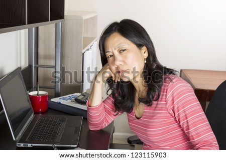 Mature Asian woman tired of doing income taxes with tax form booklet, calculator, coffee cup and computer on desk