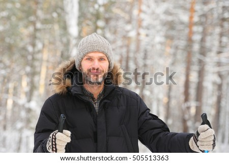 Mature bearded man in a forest with ski poles