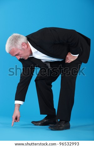 mature businessman pointing at something on floor