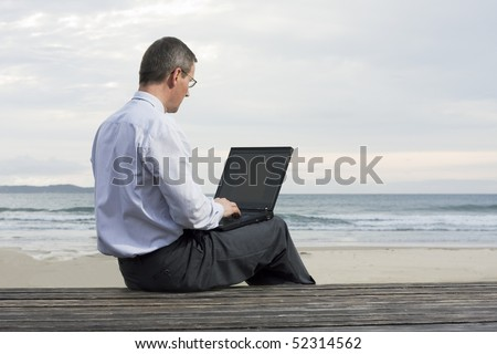 Mature businessman working with laptop on a beach