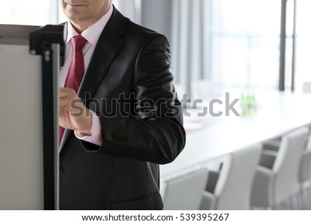 Mature businessman writing on whiteboard in board room