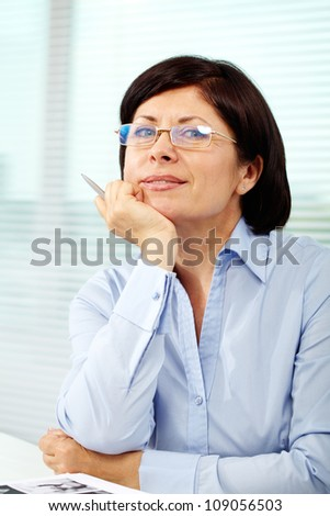 Mature businesswoman in eyeglasses looking at camera