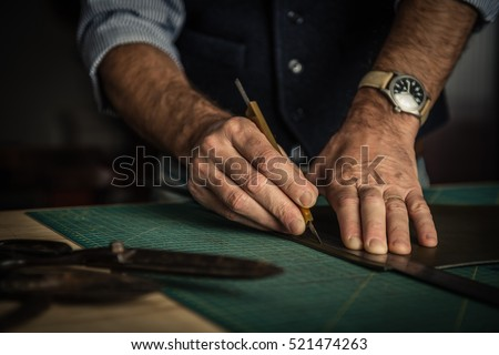 Mature caucasian leather man working as artisan in his workshop