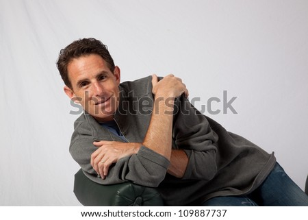 Mature Caucasian male reclining on a bench and smiling at the camera with a pleasing friendly smile
