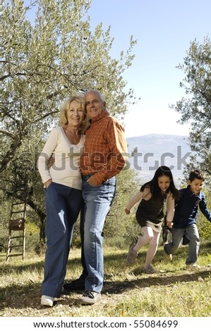 mature couple embracing while kids are running