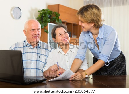 Mature couple filling questionnaire for employee with laptop of the bank