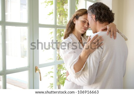 Mature couple hugging in a garden corridor at home, with their heads together.