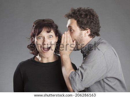 Mature couple man whispering secret in woman's ear