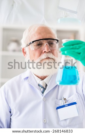 Mature laboratory worker carrying out research, focus on his face