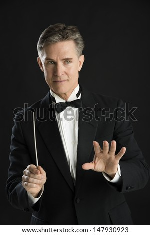 Mature male music conductor gesturing while directing with his baton against black background