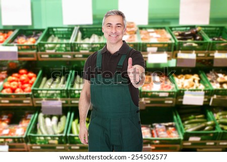 Mature Male Sales Clerk Showing Thumb Up Gesture In Supermarket
