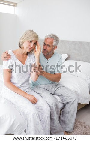 Mature man consoling tensed woman in bed at home