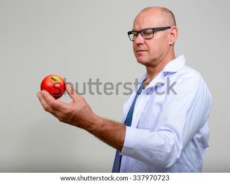 Mature man doctor holding apple