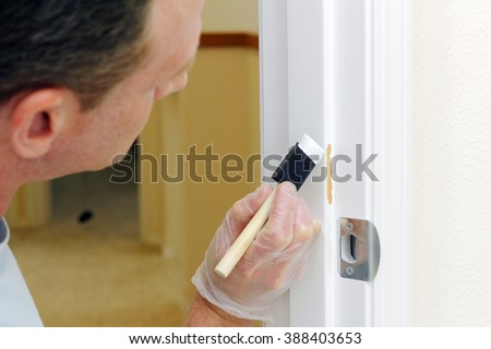 Mature man in his forties about to paint a white door jam with touch up paint.  Caucasian guy about to spread white paint on a doorway where the paint was chipped off.