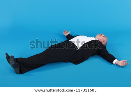 mature man in suit lying on his back with arms wide apart against blue background