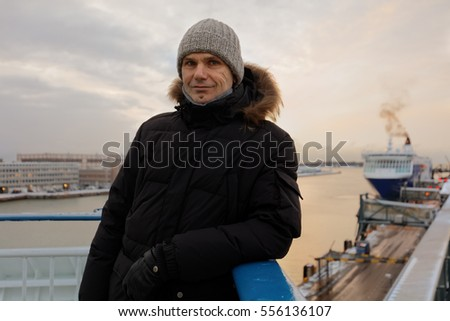 Mature man in winter clothes against departing cruiseferry ship in Helsinki, Finland