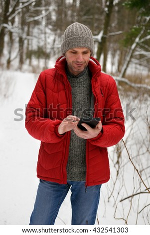 Mature man in winter clothes holding his tablet in a forest