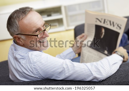 mature man with newspaper at home